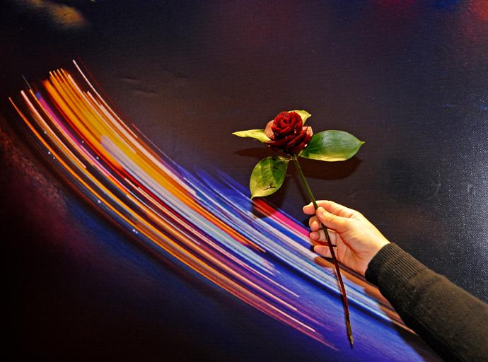 Rosa de remolacha hecha por las diestras manos de una jóven en el stand de Thailandia y fotografiada sobre el fondo de unos reflejos del rio de una ciudad china.